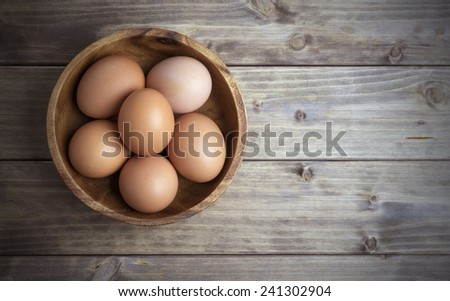 eggs in a wooden bowl on the table from the old boards - stock photo