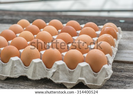 eggs in an egg carton on wooden background - stock photo