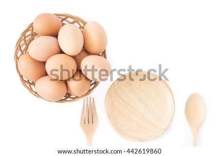 eggs in basket and wooden plate,spoon on white background - stock photo