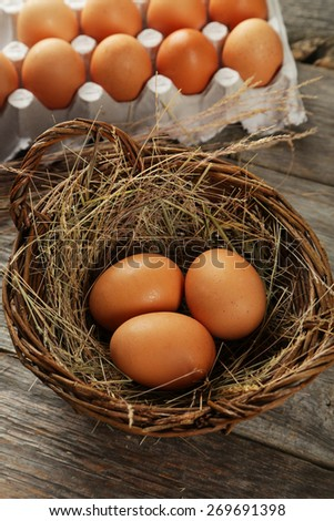 Eggs in basket on brown wooden background - stock photo