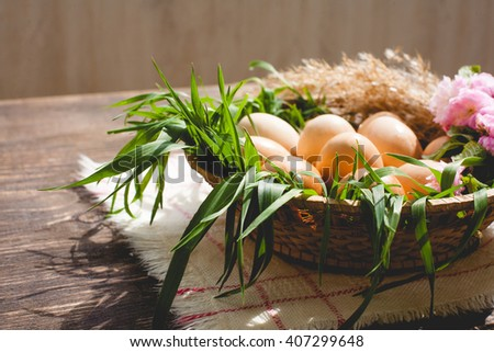 Eggs in basket with green grass and reeds on wooden board. Natural healthy food - stock photo