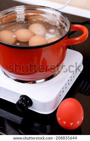 Eggs in boiling water in pan on electric hob - stock photo