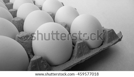 Eggs In Container Blurry Food Background - White eggs in a cardboard container, blurry black and white raw food background photo.