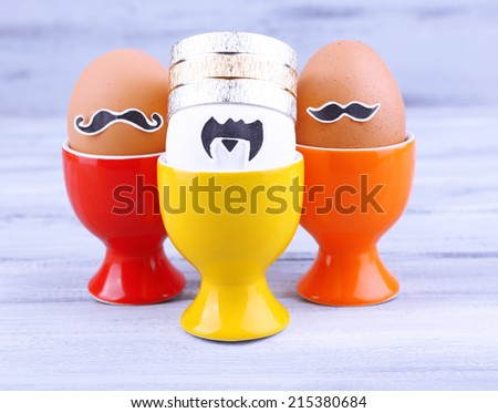 Eggs in egg cups on grey wooden background - stock photo