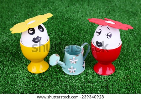 Eggs in egg cups with watering can on green background - stock photo