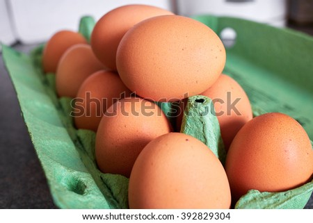 Eggs in green cardboard packaging, placed on kitchen top - stock photo