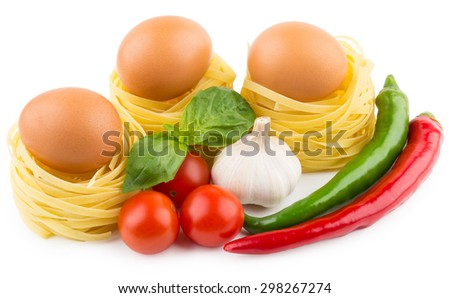 Eggs in nest from pasta, tomatoes, garlic and chili peppers isolated on white background - stock photo