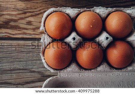 eggs in paper on wooden background - stock photo