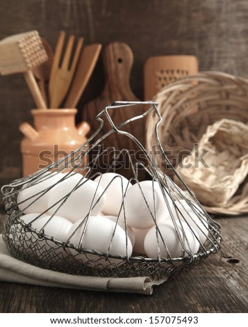 Eggs in the Basket and kitchen cooking utensils, toned
