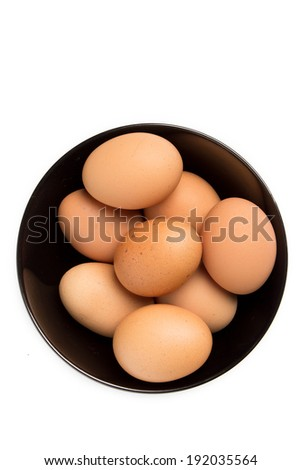 Eggs in the black bowl on isolated background - stock photo