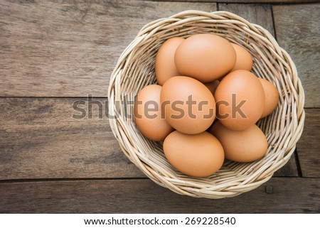 Eggs in wicker basket on old wooden table  - stock photo