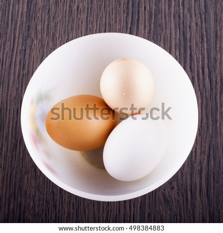 Eggs of three colors in a cup, square image
