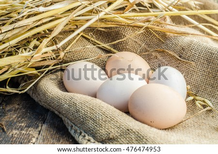 Eggs on a wooden background and straw