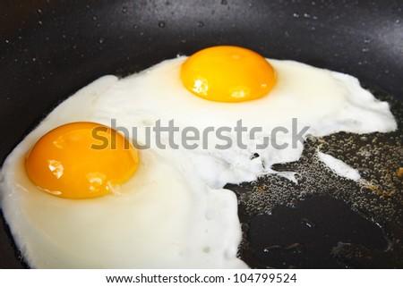 eggs on black pan - stock photo