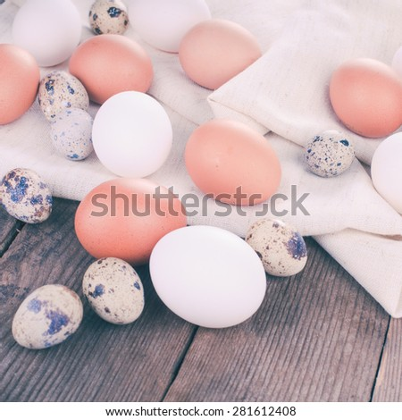 Eggs on textile tablecloth over rustic wooden table - stock photo