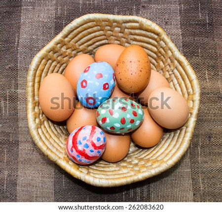 Eggs, painted eggs for Easter in basket on brown cotton background - stock photo