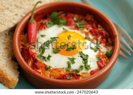 Eggs poached in tomato sauce and other vegetables served with bread.