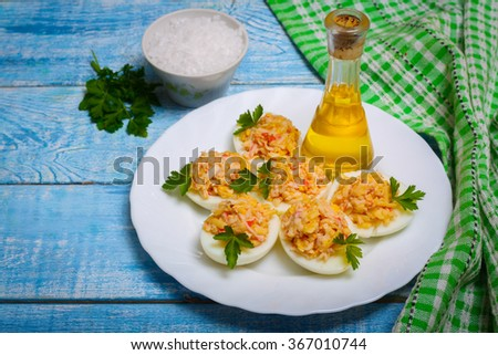 Eggs stuffed with crab and cheese on a wooden table - stock photo