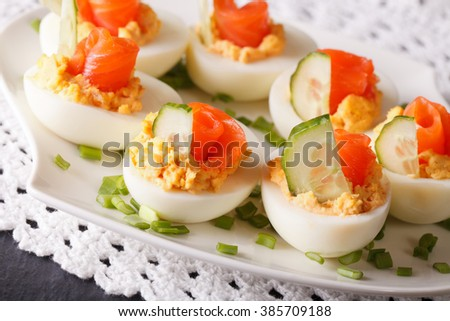 Eggs stuffed with salmon and cucumber closeup on a plate on the table. horizontal