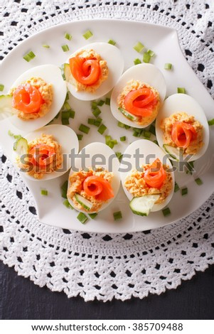 Eggs stuffed with salmon, cheese and cucumber closeup on a table. vertical view from above
