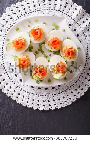 Eggs stuffed with salmon, cheese and cucumber on a table. vertical view from above