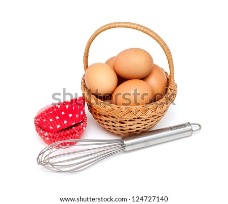 eggs, whisk and cupcake liners over white - stock photo