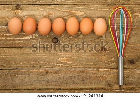 Eggs with kitchen whisk on a vintage wooden background with copy space - stock photo
