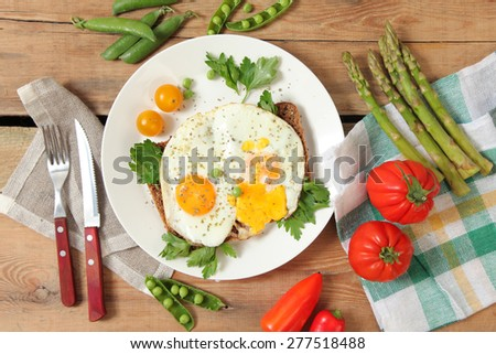 eggs with vegetables on wooden table - stock photo