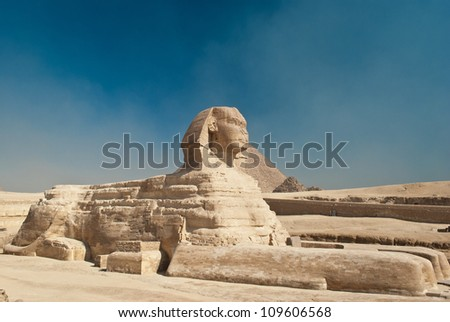 egiptian sphinx in desert near old pyramid - stock photo