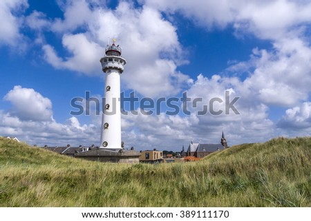 Egmond, the Netherlands, August 5, 2010; White lighthouse in the dunes with church and houses in the background under a beautiful sky