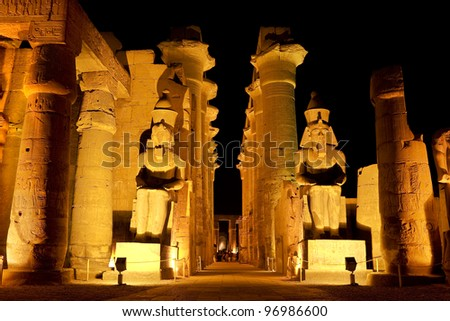 Egypt. Illuminated Luxor Temple. The peristyle courtyard of Ramesses II with two seated granite statues and the processional colonnade of Amenhotep III - stock photo