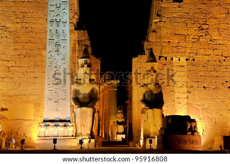 Egypt. Illuminated Luxor Temple. The red granite obelisk and two seated statues of Ramesses II in front of the first pylon - stock photo