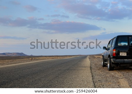 EGYPT, SAHARA - DEC 28, 2008: Off-road car shown on the road in desert at sunset. Extreme desert safari is one of the main local tourist attraction in Egypt - stock photo