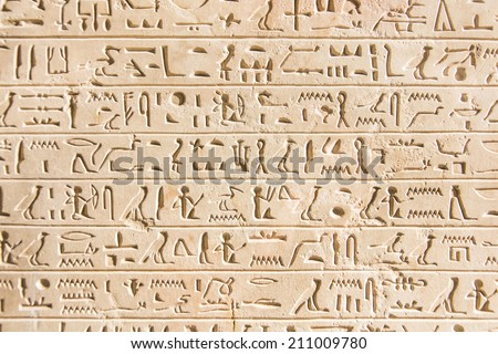 Egyptian hieroglyphs engraved on an ancient stone wall  - stock photo