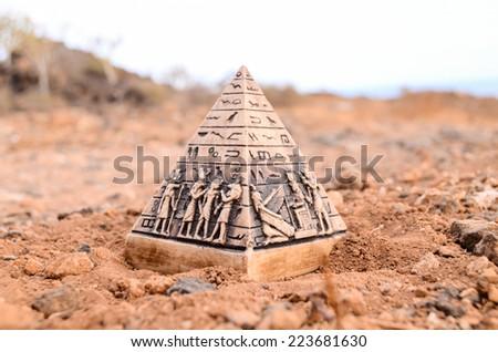 Egyptian Pyramid Model Miniature in the Rock Desert - stock photo