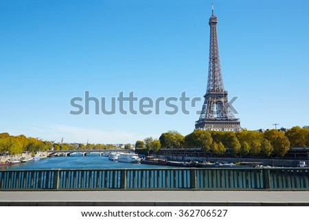 Eiffel tower and empty sidewalk bridge on Seine river in a clear sunny day, autumn in Paris