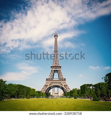 Eiffel Tower and gardens with people walking against blue cloudy sky. Paris, France. Filtered image instagram style. - stock photo