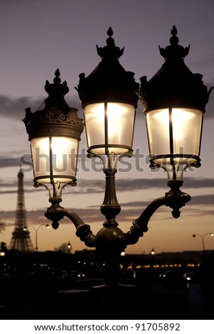 Eiffel Tower and illuminated at night in Paris, France - stock photo