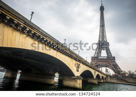 Eiffel tower and Jena bridge in a cloudy day - stock photo