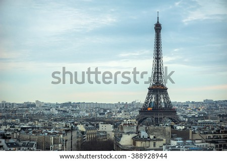 Eiffel tower and Paris roofs at dusk, Paris, France - stock photo
