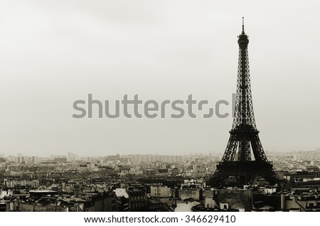 Eiffel tower and Paris roofs view on cloudy day in black and white - stock photo