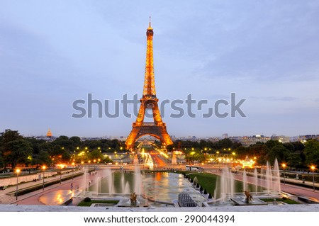 Eiffel tower at sunset with lights on, in Paris - stock photo
