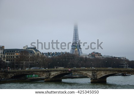 Eiffel tower disappearing in the mist at cloudy winter evening. Black and white. - stock photo