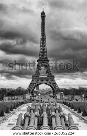 Eiffel tower in a cloudy sky in black and white - stock photo