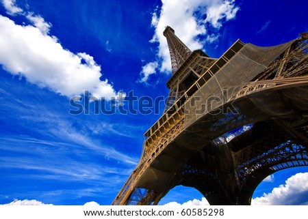 Eiffel tower in Paris, France, against an intense blue sky with white clouds