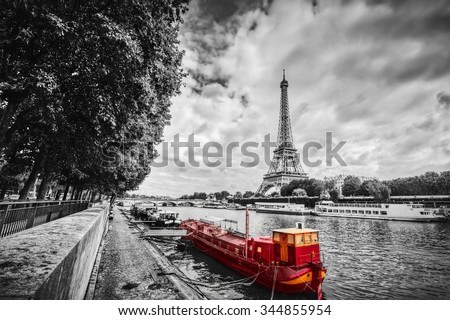 Eiffel Tower over Seine river in Paris, France. Red tourist ship on water. Vintage, black and white. - stock photo