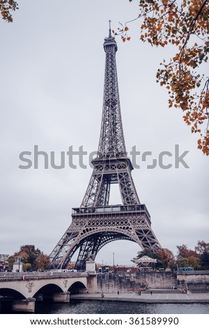 Eiffel Tower, Paris, France on a misty autumn day viewed between the colorful bright yellow fall foliage on the trees below