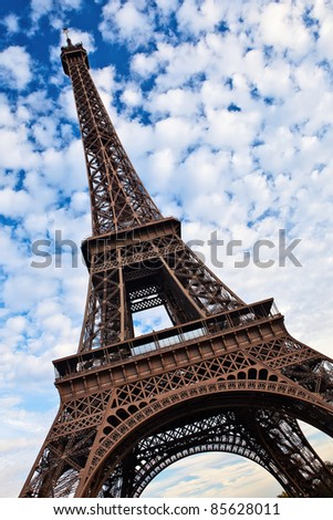 Eiffel tower tilted view over blue sky with white clouds.
