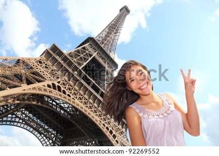 Eiffel Tower tourist posing smiling by Eiffel Tower, Paris, France during Europe travel trip. Young happy excited multiracial Asian Caucasian woman in her 20s.