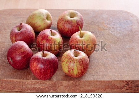 Eight apples on a wooden board - stock photo